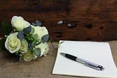 与玫瑰色花和笔记本的静物画在麻袋布 库存照片