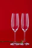 与玫瑰色花的两个酒杯在红色 免版税库存图片