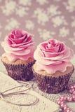 与玫瑰色花的两块杯形蛋糕 免版税库存照片