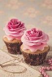 与玫瑰色花的两块杯形蛋糕 免版税库存图片