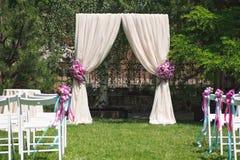 与玫瑰色花的豪华婚礼曲拱 库存图片
