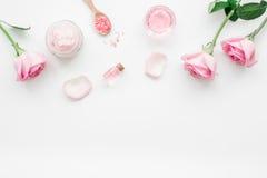 与玫瑰色花的身体治疗和文本的化妆用品集合白色书桌背景顶视图空间 库存图片
