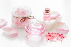 与玫瑰色花萃取物和化妆用品的温泉集合在白色书桌背景的身体的 库存照片