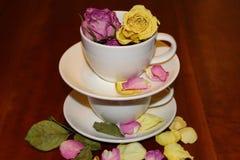 与玫瑰色芽和玫瑰花瓣的被堆积的茶杯 免版税库存图片