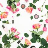 与玫瑰花和女性化妆用品的花卉框架在白色背景 平的位置,顶视图 库存图片
