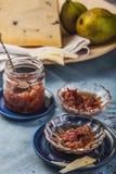 与玫瑰花瓣的小果酱盘阻塞,梨和乳酪一个大片断在绿松石桌布的 库存图片