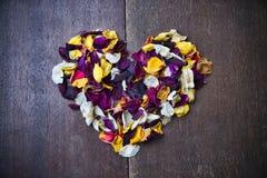 与玫瑰花瓣的心脏的背景为情人节 免版税库存照片