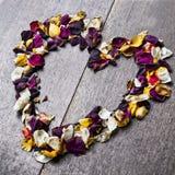 与玫瑰花瓣的心脏的背景为情人节 免版税库存图片