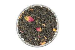 与玫瑰花瓣的茶叶在一个玻璃杯子 免版税库存照片