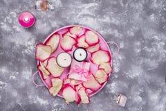 与玫瑰花瓣的蜡烛在桃红色盘子 图库摄影