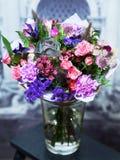 与玫瑰,在一个玻璃花瓶的蓝色花的花束 免版税库存图片