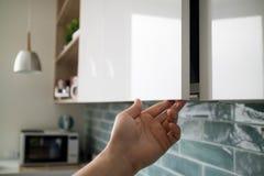 与现代家具的厨房内部 人打开厨房的一个现代垂悬的内阁,不用门把手 库存图片