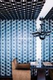 与现代豪华墙壁装饰的餐厅餐桌 库存图片