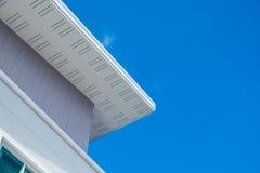与现代房子天花板和屋顶的白色房檐反对蓝色s的 免版税库存图片