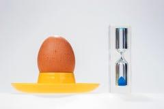 与现代玻璃蛋定时器的鸡鸡蛋 图库摄影