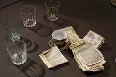 与玻璃、咖啡杯和金钱的表 库存照片