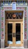 与玻璃和多彩多姿的灰泥o的外部木前门 免版税库存图片