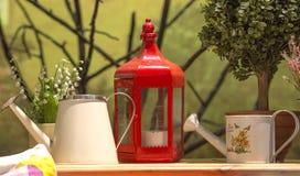 与玻璃墙烛台的红色金属有反对绿色墙壁背景的白色蜡烛里面和两个白色喷壶的 免版税图库摄影