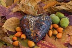 与玻璃心脏的秋天静物画 免版税库存图片