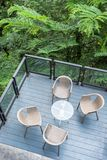 与玻璃桌的木椅子在露台在庭院里 库存图片