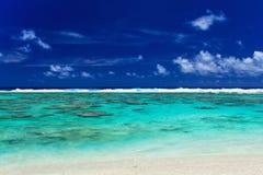 与珊瑚礁和海浪的热带海滩在库克群岛挥动 免版税图库摄影