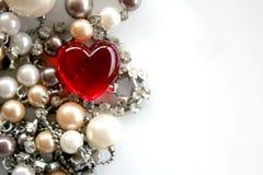 与珍珠和银色链子的红色玻璃心脏 免版税库存照片