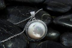 与珍珠层的人造白金在黑石头的垂饰和金刚石 免版税库存图片