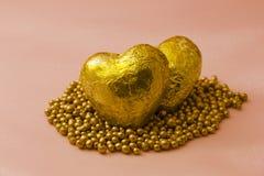 与珍珠的金黄心脏在他们附近 免版税库存图片