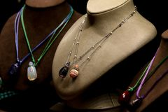 与珠宝石头和链子的专属银色项链在时装模特照片 免版税库存照片