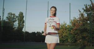 与球拍一女运动员的打的网球网球场的,她穿精密网球衣裳 影视素材