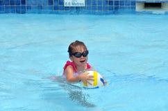 与球的儿童游戏在游泳池 免版税库存图片