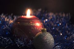 与球的圣诞节蜡烛和在黑暗的一本诗歌选 免版税库存照片