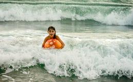 与球的小女孩游泳在波浪的海洋 库存图片