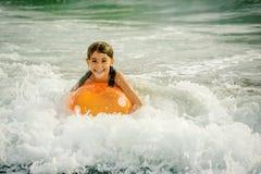 与球的小女孩游泳在波浪的海洋 免版税库存照片