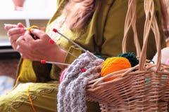 与球的篮子毛线和妇女编织 免版税库存照片