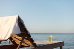 与球衣和杯的Sunbed对此的冷的饮料在海海滩 免版税库存图片