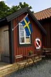 与瑞典旗子的海滩小屋和Lifebuoy在瑞典 库存图片