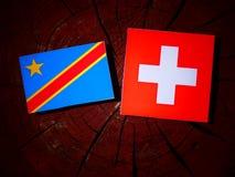 与瑞士旗子的刚果民主共和国旗子在树 免版税图库摄影