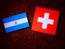 与瑞士旗子的尼加拉瓜的旗子在被隔绝的树桩 库存例证