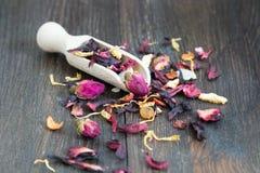 与瓣和草本的干茶在木匙子 图库摄影