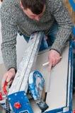 与瓦片切割机的承包商 免版税库存照片