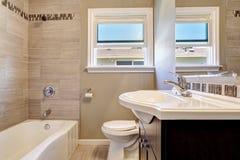 与瓦片墙壁修剪的空的卫生间内部在软的米黄颜色 库存照片