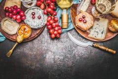 与瓶的各种各样的美好的乳酪选择酒,蜂蜜芥末酱和葡萄在土气背景,顶视图 免版税图库摄影