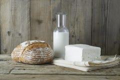 与瓶的新鲜的希腊白软干酪牛奶和面包 免版税图库摄影
