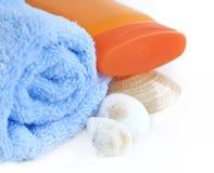 与瓶的蓝色毛巾sunblock和海运壳 免版税库存照片