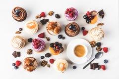 与甜杯形蛋糕、茶匙和咖啡的安排的平的位置 免版税库存图片