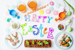 与甜点和汁液的愉快的复活节词孩子的 库存照片