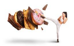 与甜点和糖果战斗的适合的少妇 图库摄影