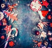 与甜点和红色假日装饰的圣诞节背景:圣诞老人帽子,树,星,球,顶视图 免版税图库摄影