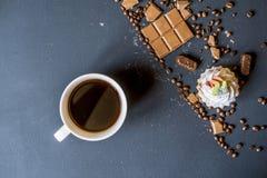 与甜点和饼干的咖啡在黑暗的桌f上 图库摄影